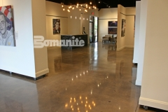 Bomanite Patene Teres custom polished concrete was installed here with a high-gloss finish that adds a warm, glowing design aesthetic to highlight the memorial portraiture that was created as part of The American Fallen Soldiers Project.