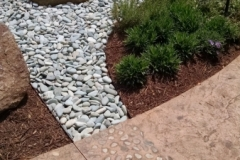 Bomanite Bomacron Regular Slate imprinted concrete was installed here with strategically placed stones to create a hardscape walkway with beautiful texture and color that enhances the tranquil setting in this healing garden.
