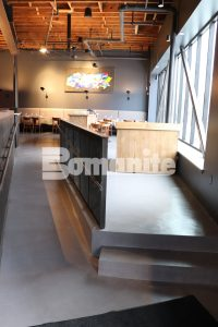 A view of a raised seating area and a long expanse of decorative concrete flooring of Bomanite Toppings Systems using Bomanite Micro Top at Elmwood in Maplewood, MO, installed by Musselman and Hall.
